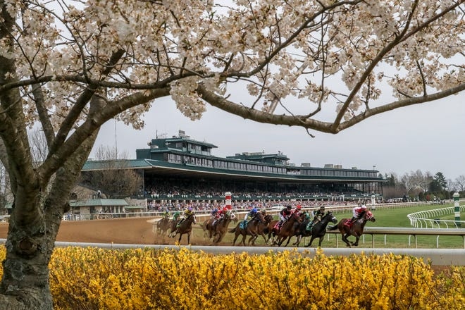 Horses round the turn in the third race on the opening day of the spring meet at Keeneland.