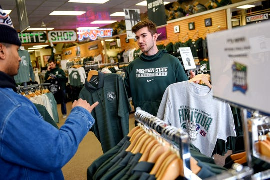 Michigan State University junior Garrett Brown, right, holds up two potential options as his friend and fellow junior Jordan Haber gives his input while the two shop for Final Four merchandise at the Student Book Store on Thursday, April 4, 2019, in East Lansing.