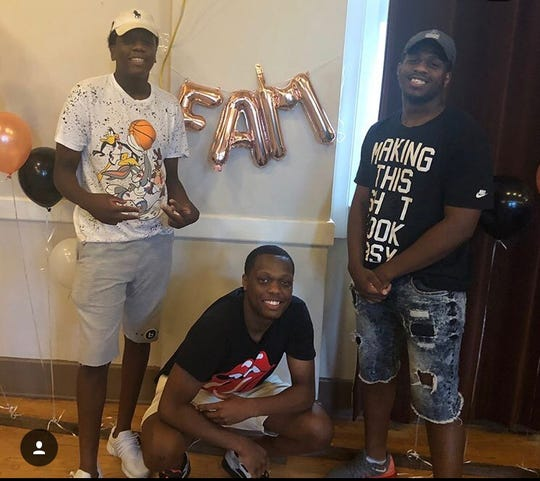 Michigan State point guard Cassius Winston (center) poses for a photo with his brothers Khy (left) and Zach (right).