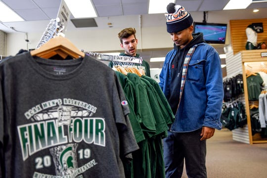 Michigan State University juniors Garrett Brown, left, and Jordan Haber shop for Final Four merchandise at the Student Book Store on Thursday, April 4, 2019, in East Lansing.