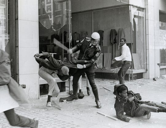 "March 28, 1968 - Larry Payne, white shirt on right, is photographed in front of a Main Street tailor shop as part of the riots taking place during the sanitation workers' strike.  The officer, identified as Policeman Michael Patrick, strikes an individual identified as ""Spaceman.""  Jerry Lee Sanders, is pictured on the ground in front of Patrick."