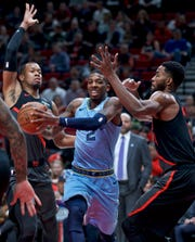 Memphis Grizzlies guard Delon Wright, center, drives to the basket past Portland Trail Blazers guard Rodney Hood, left, and forward Maurice Harkless, right, during the first half of an NBA basketball game in Portland, Ore., Wednesday, April 3, 2019. (AP Photo/Craig Mitchelldyer)