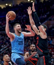 Memphis Grizzlies forward Chandler Parsons, left, shoots as Portland Trail Blazers center Enes Kanter defends during the first half of an NBA basketball game in Portland, Ore., Wednesday, April 3, 2019. (AP Photo/Craig Mitchelldyer)