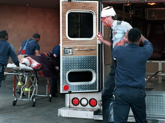 Federal Express pilot David G. Sanders is helped from an ambulance at a Memphis hospital on April 7, 1994. He was among three crewmen attacked by another FedEx employee shortly after a company DC-10 took off from Memphis.
