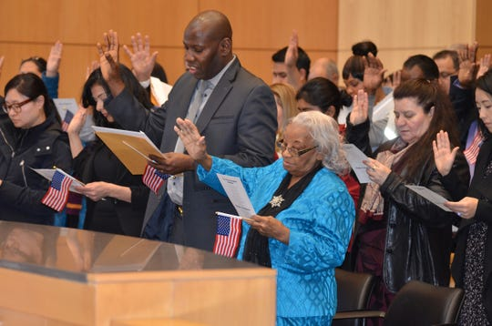 Uctorieuse Destin and 91 other new citizens raise their right hands during a naturalization ceremony in a New York federal courthouse.