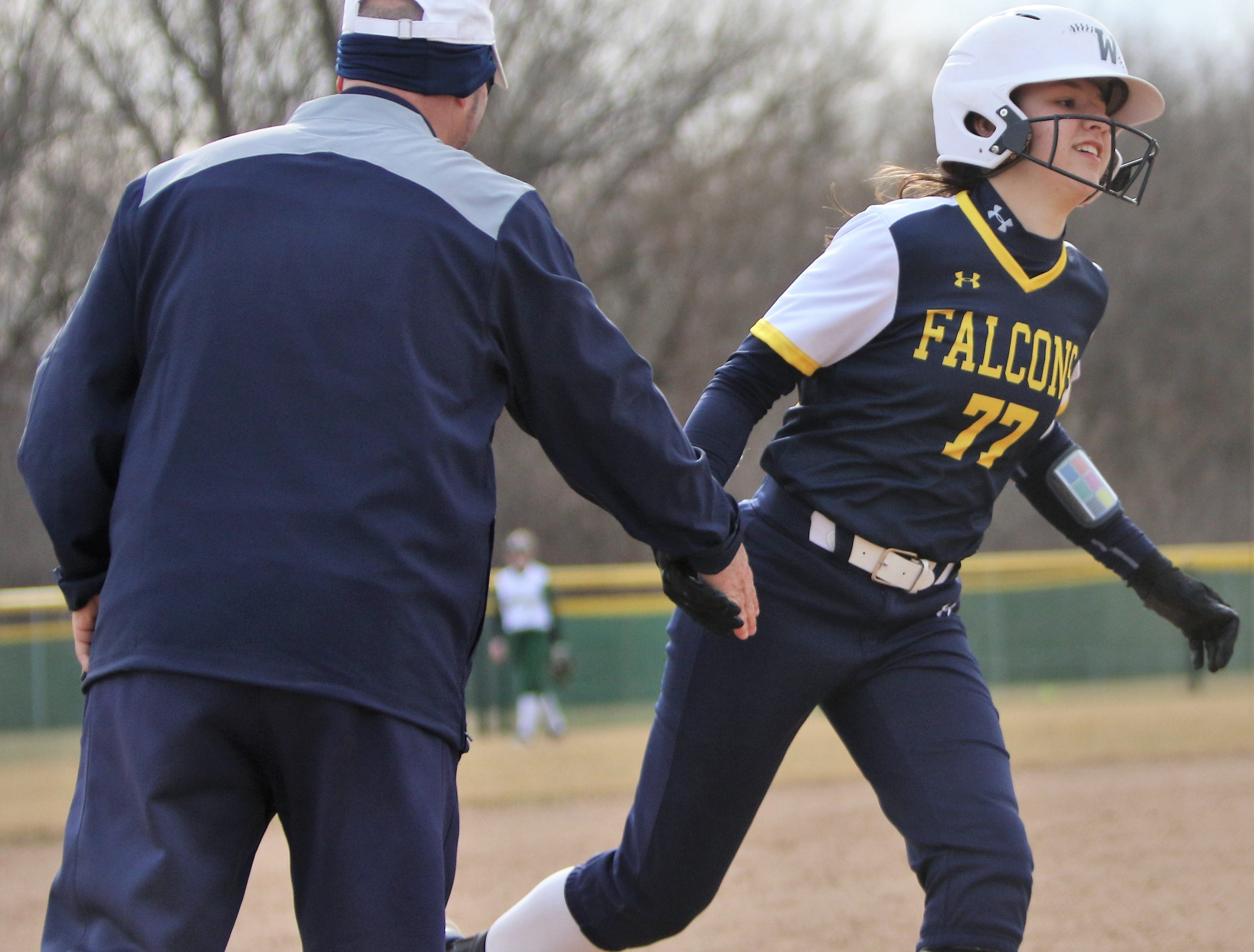 Whitnall sophomore Jesicca Vallier is congratulated by head coach John Quinlan after hitting a home run against Greenfield on April 3, 2019.