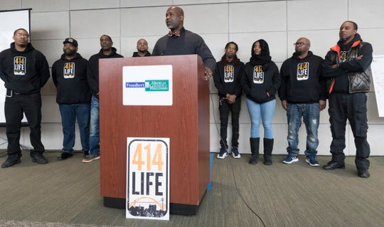 """Derrick Rogers, program director 414 LIFE, Uniting Garden Homes Inc. is flanked by people trained as violence interrupters during a news conference about a new violence prevention program Thursday, April 4 2019 at Froedtert & the Medical College of Wisconsin – Clinical Cancer Center, 8800 W. Doyne Ave. in Milwaukee, Wis. The City of Milwaukee Health Department's Office of Violence Prevention is teaming with Froedtert & the Medical College of Wisconsin and Ascension Wisconsin that will use people trained as """"violence interrupters"""", employing a  prevention-based outreach and targeted conflict mediation."""