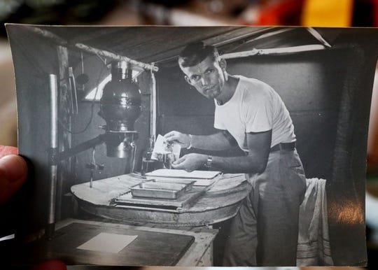 Jake Skocir makes a print in a tent darkroom while serving in the Pacific during World War II.