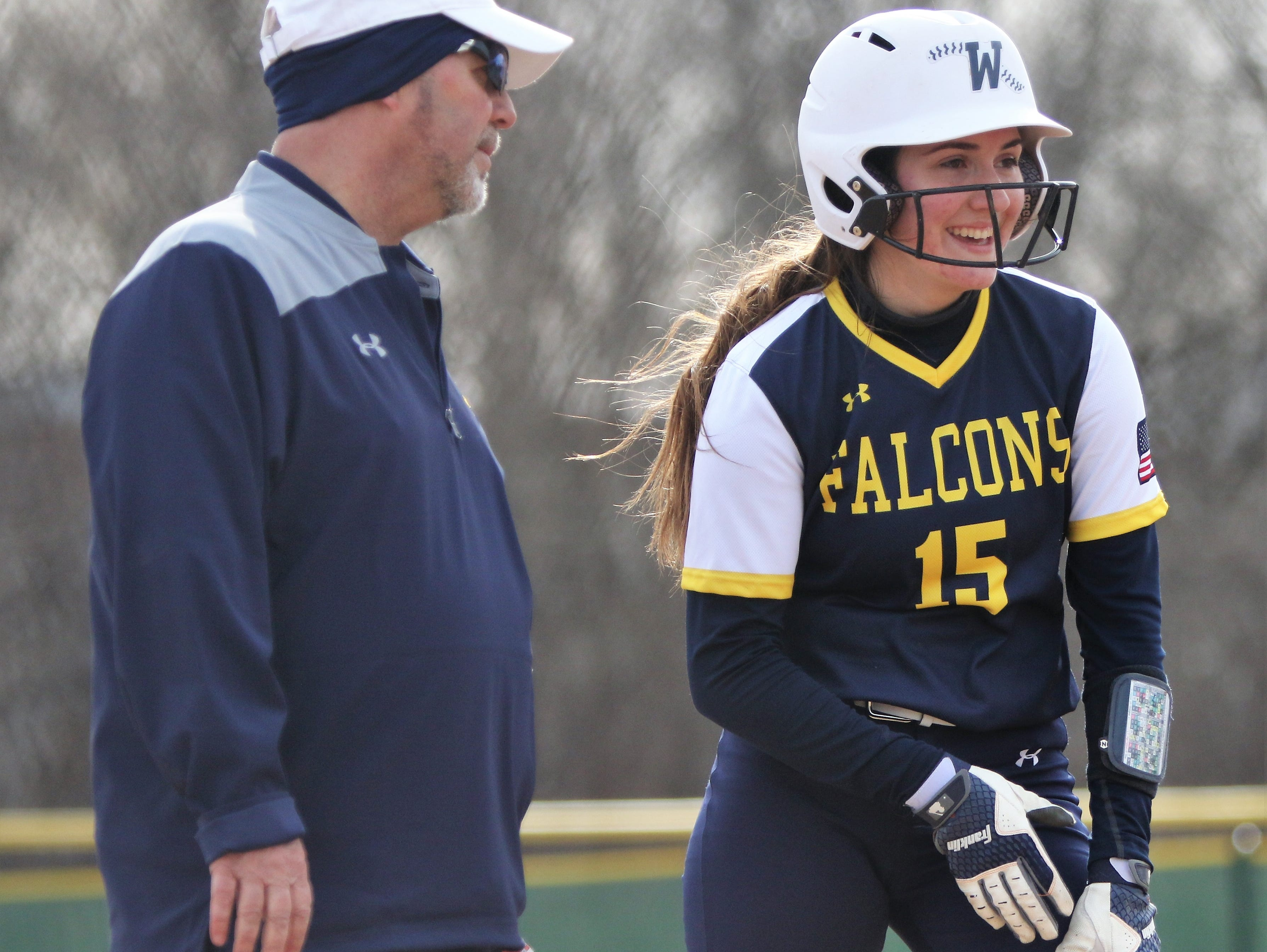 Whitnall head coach John Quinlan and junior Alyssa Trensch convene at third base during the Falcons' season-opening game against Greenfield on April 3, 2019.