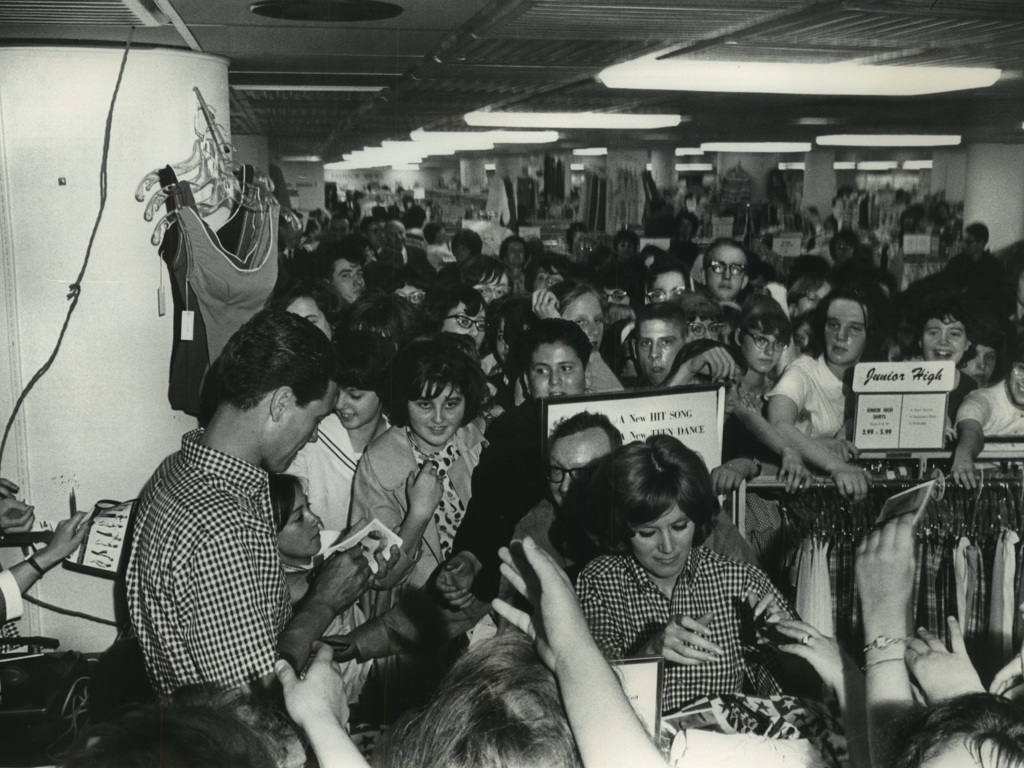 Television stars Roger Smith and Kathy Nolan signed autographs, May 17, 1964, for a throng of teenagers in the basement of the Boston Store.