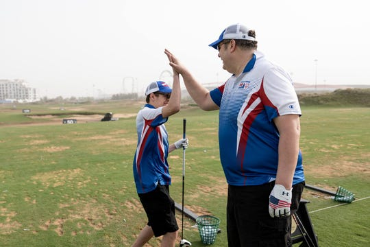 Ryon Knodl, leftl, and player-coach Ken Kuemmerlein high-five after practicing their golf game for the Special Olympics World Games in Abu Dhabi in March. The pair came home to southeastern Wisconsin with a bronze medal.