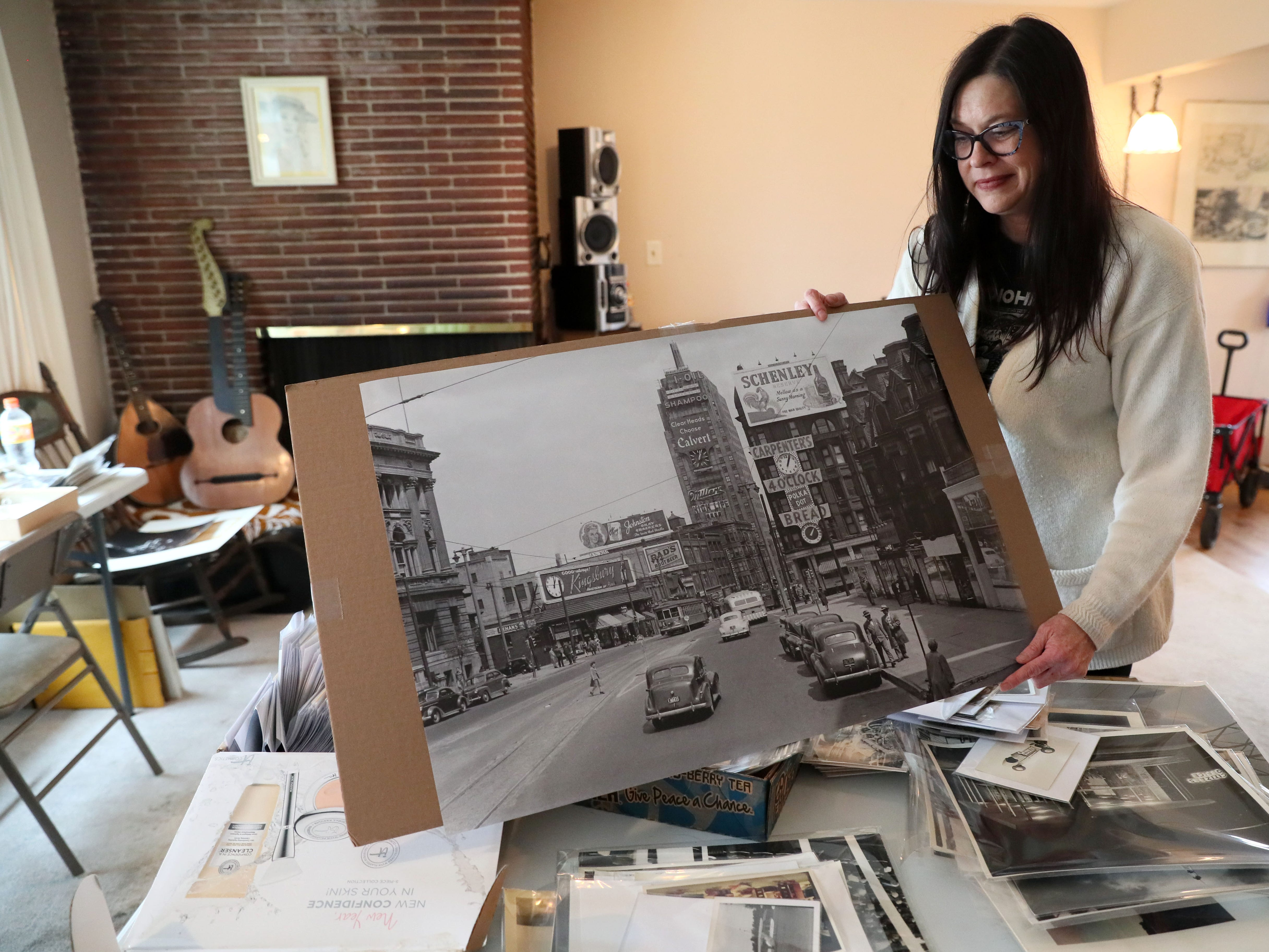 Jennie Lovejoy,  owner of Attic Addict,  shows a large photograph taken by Jake Skocir of Wisconsin Avenue in downtown Milwaukee post World War II. Skocir died a decade ago and left behind around 6,000 black and white photos. They are among the items being sold at an estate sale. The photos also are being featured in a gallery night event on April 11.