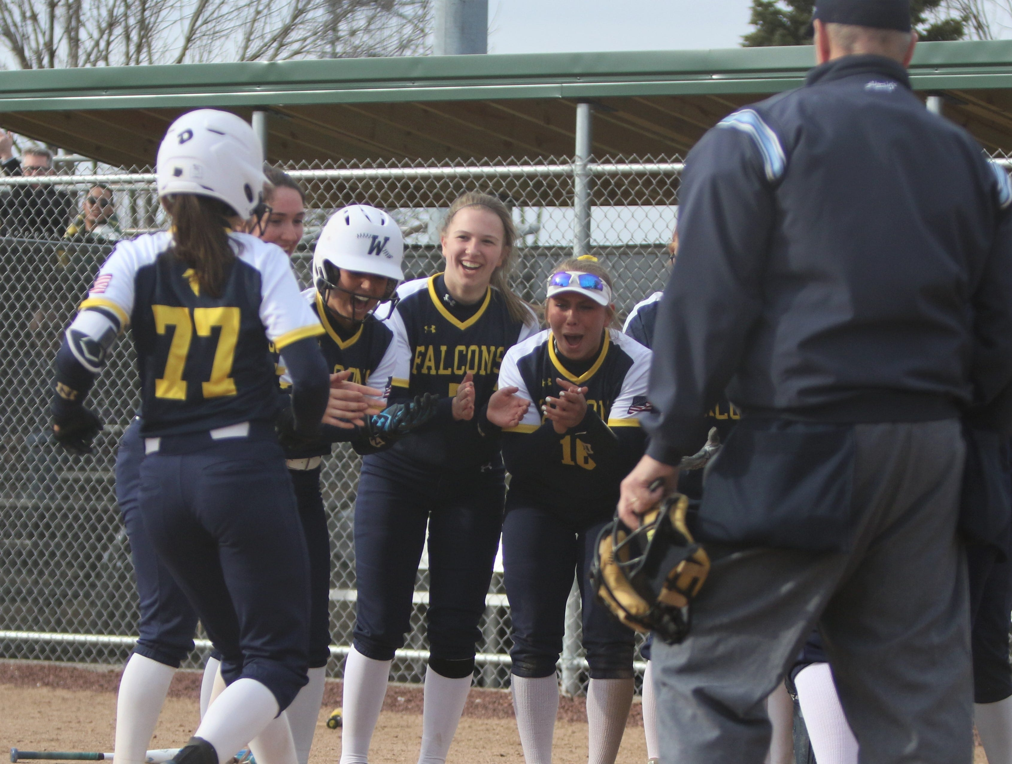 Whitnall players await Jesicca Vallier at home plate after Vallier's home run against Greenfield on April 3, 2019.