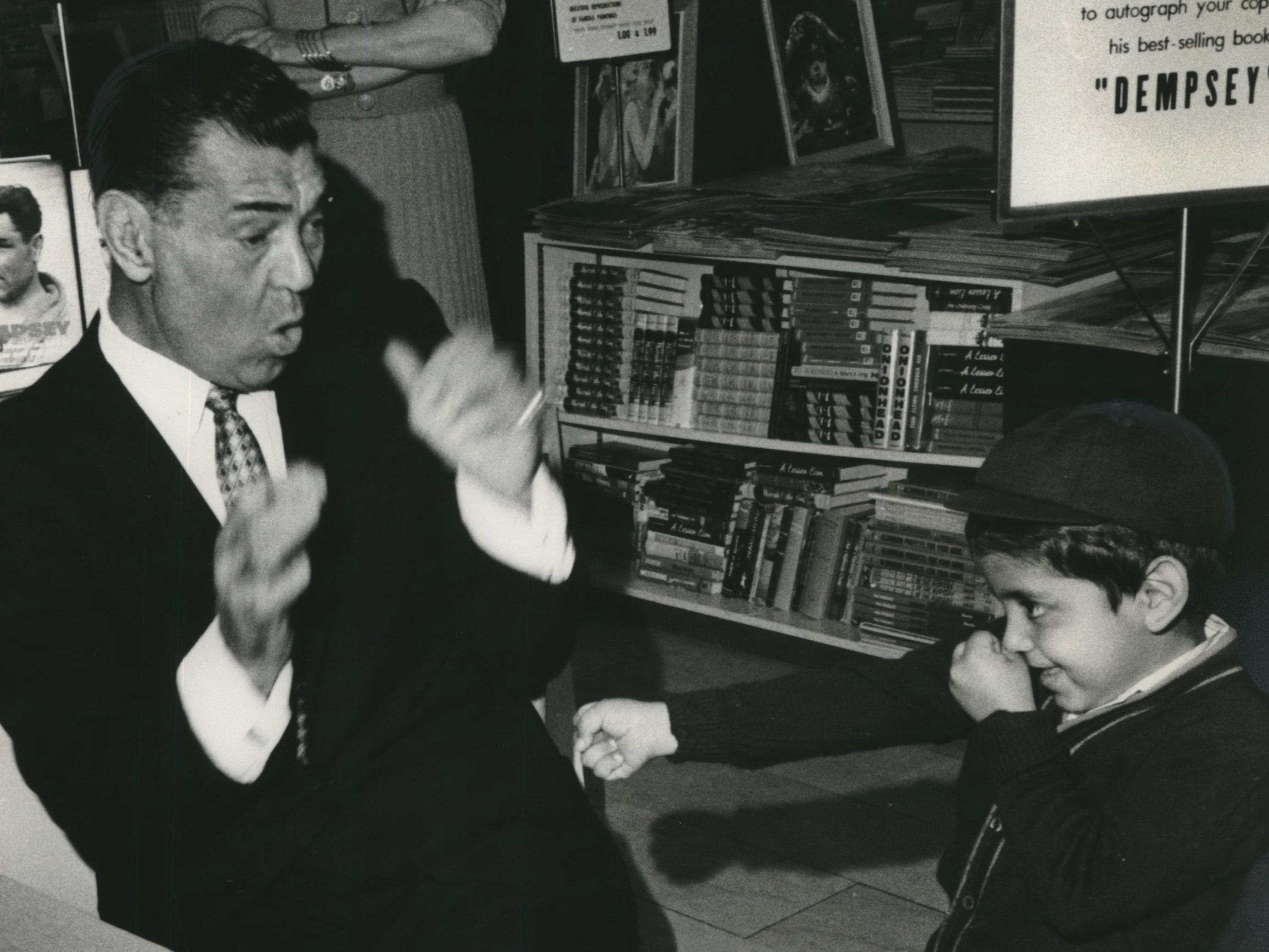 """Look Out, Champ! Look out behind you, Jack! The little fellow, ready to take on the great former heavyweight champion, Jack Dempsey, is 4-year-old Ruben Velazquez, who was at the Boston Store May 20, 1960, where Jack was busy autographing copies of his book. """"Dempsey,"""" by Bob Considine and Bill Slocum, Hearst Headline Service writers."""