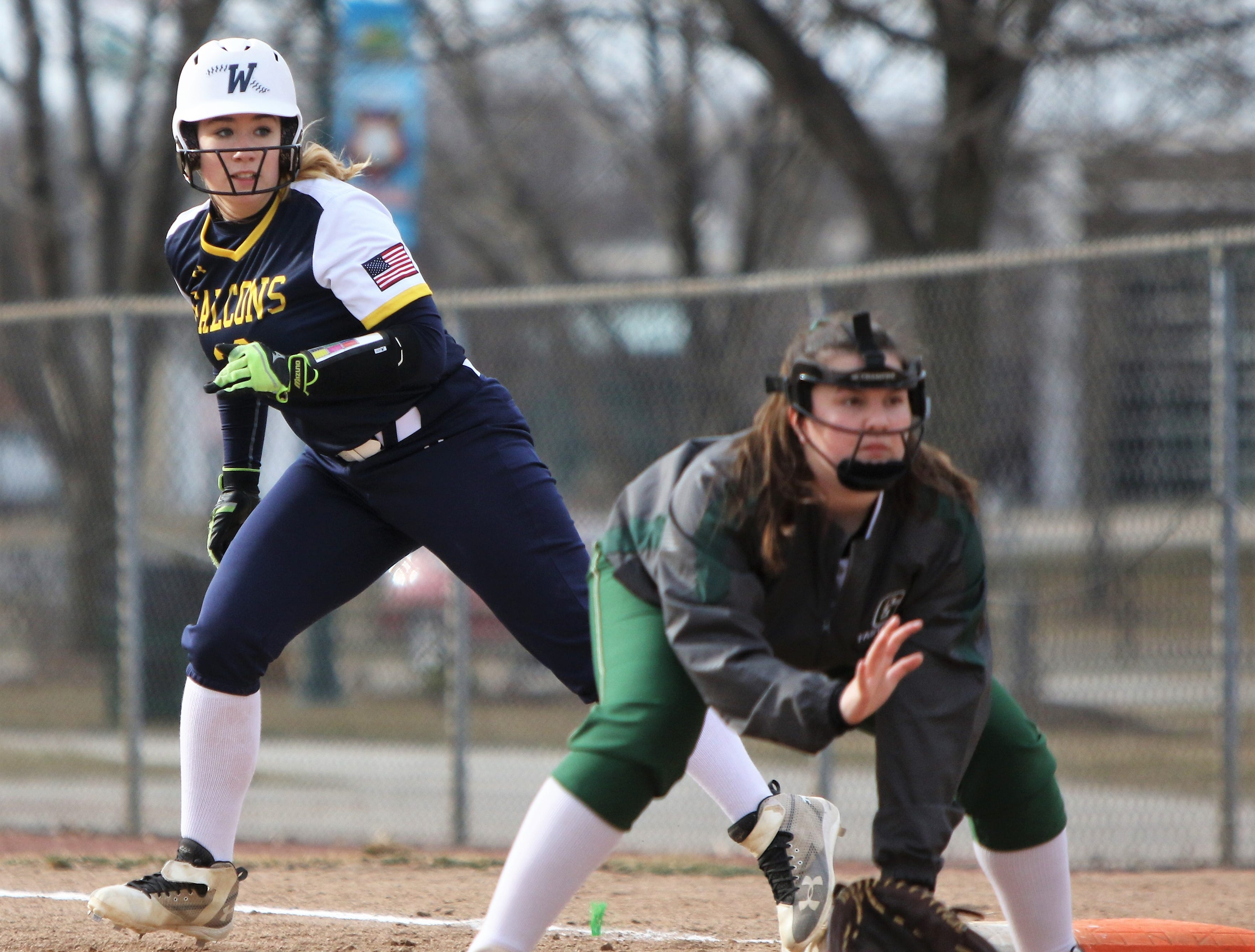 Whitnall's Kayla Hartig (back) takes her lead off of first base in a game against Greenfield on April 3, 2019.