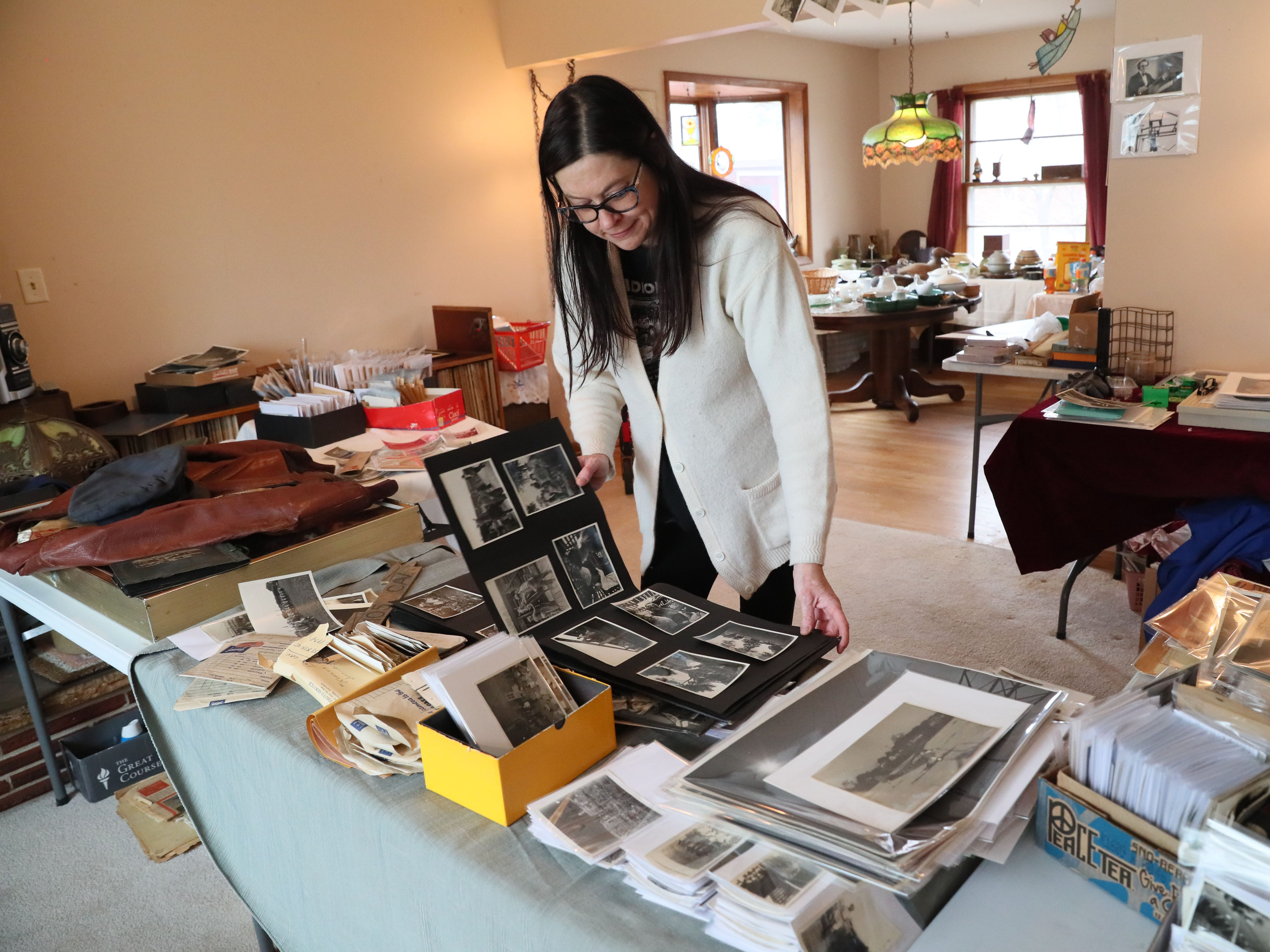 Jennie Lovejoy, owner of Attic Addict, goes through some of Jake Skocir's photos as she readies his belongings for an estate sale.