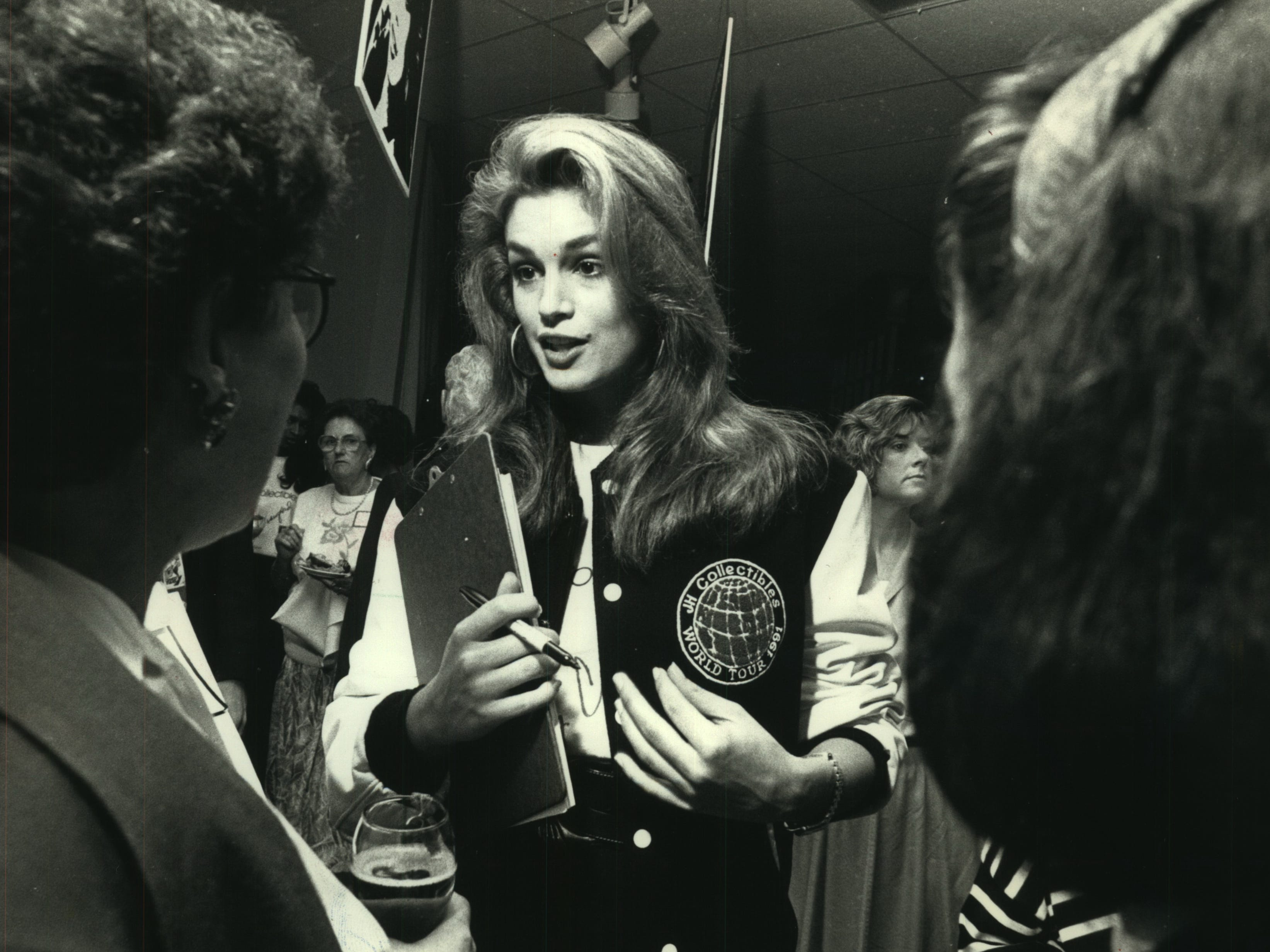 """Supermodel Cindy Crawford chats with fans at Mayfair Mall's Boston Store, September 8, 1991. Crawford was helping to promote the JH Collectibles line of clothing. Asked if she and her man, actor Richard Gere, plan to marry, Crawford said, 'He hasn't asked yet.' And if he did? I'd probably say 'yes,"""" she said."""