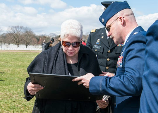 Lt. Col. Rob Stimpson, 100th Fighter Squadron commander, presents Marla Andrews, daughter of Capt. Lawrence E. Dickson, with an F-16 lithograph after a full military honors funeral and a Missing Man Formation flyover by the Red Tails, March 22, 2019, at Arlington National Cemetery, Va.