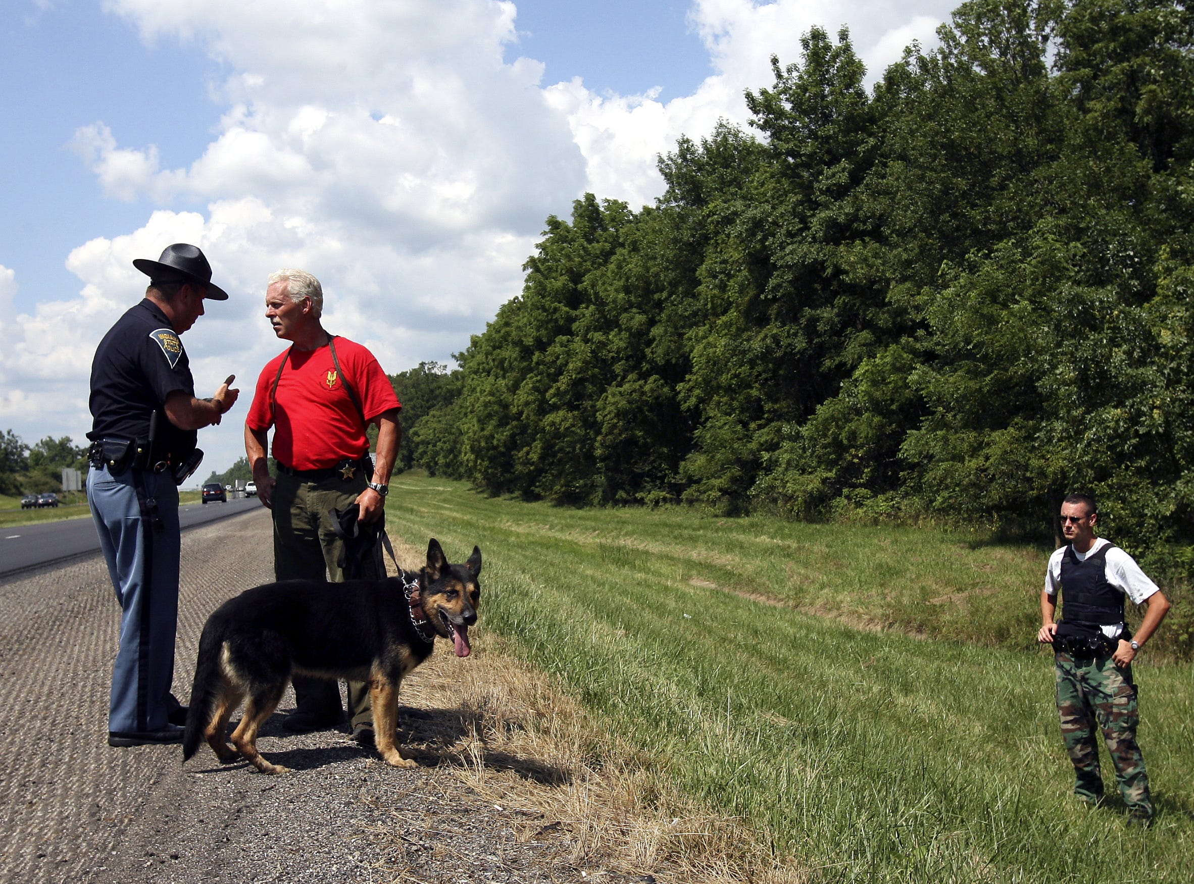FROM 2006: Sheriff George Sheridan talks with Indiana State Police Sergeant Rod Russell while a state trooper looks on after a sniper reportedly fired a gunshot at a semi as it traveled on Interstate 69 in western Delaware County.
