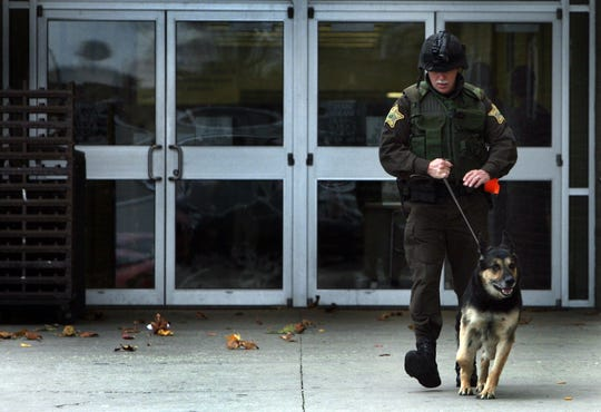 FROM 2007: Delaware County Sheriff George Sheridan leaves Northside Middle School with his K-9, Heri, after searching the building following a bomb threat.