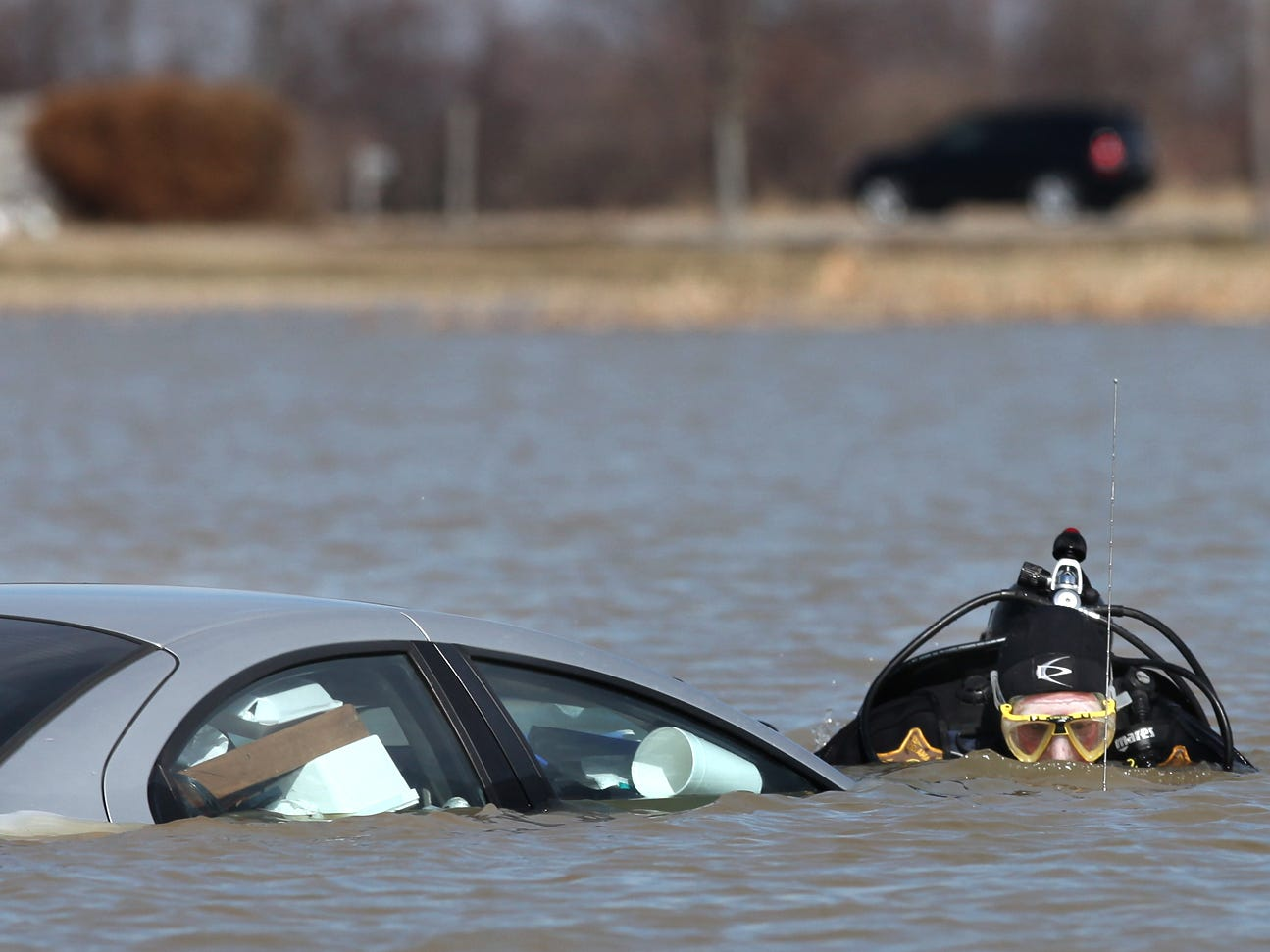 FROM 2011: George Sheridan of the Delaware County Sheriff's Department's dive team investigates a Dodge Neon largely submerged in overflowing wetlands at Ind. 28 and Delaware County Road 400-W.