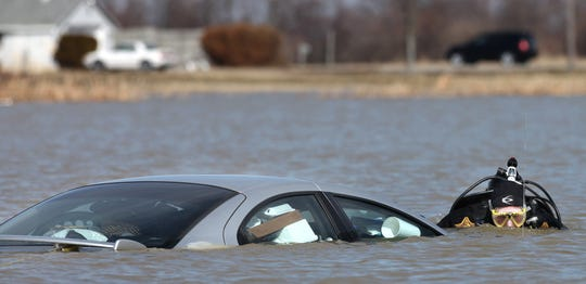 FROM 2011: Captain George Sheridan of the Delaware County Sheriff's Department's dive team investigates a Dodge Neon largely submerged in overflowing wetlands at Ind. 28 and Delaware County Road 400-W.