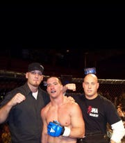 MTSU strength and conditioning coach Matt Hickmann, middle, poses for a photo after winning his first amateur MMA fight.