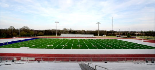 The AstroTurf company works on installing rolls of turf onto the Blackman football field, on Wednesday April 3, 2019, as the installation process continues.