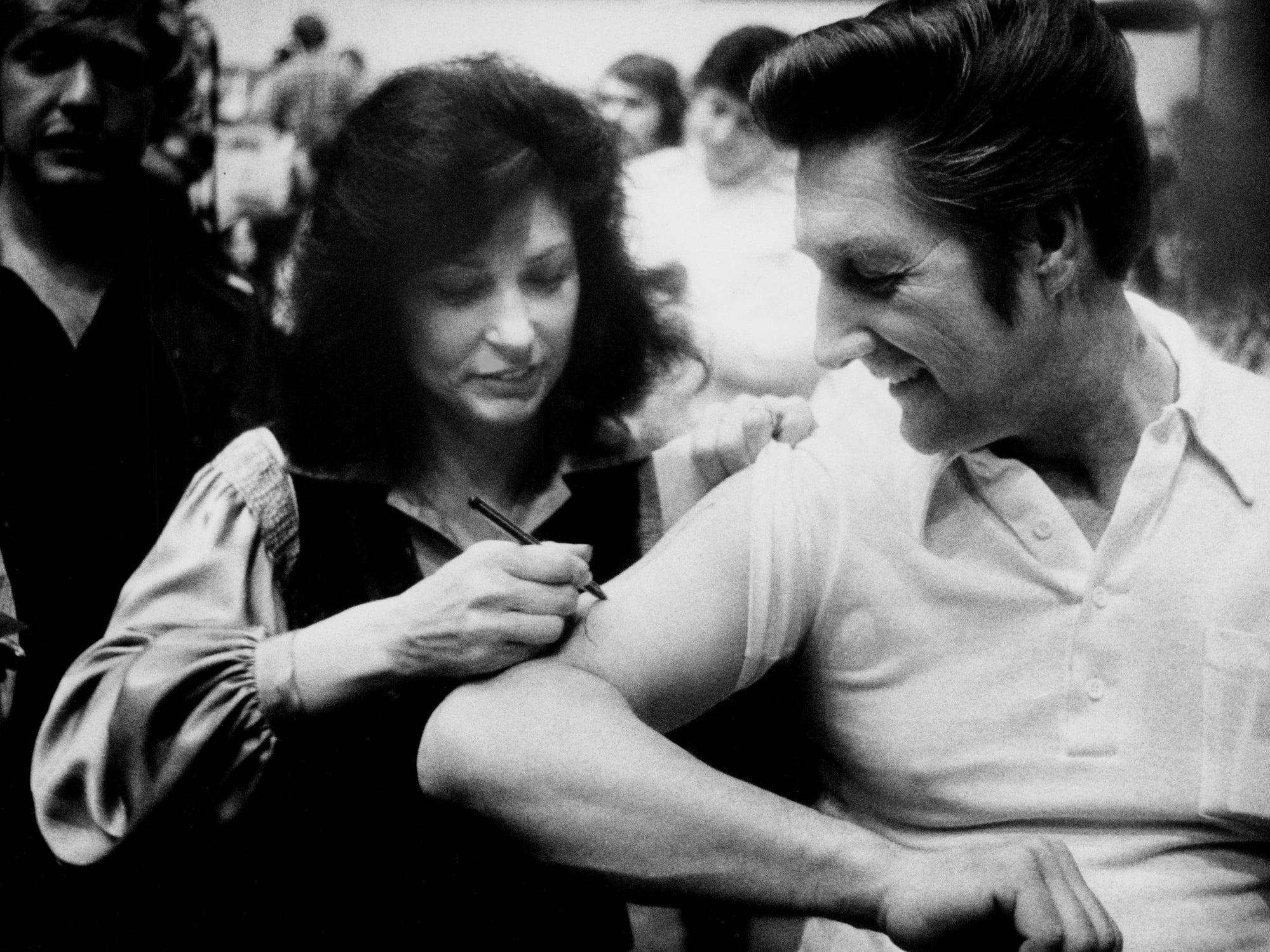 """Loretta Lynn, center, signs a autograph on the arm of a fan during a break in the filming of one of the biggest scenes in """"Coal Miner's Daughter"""" in Nashville on April 24, 1979."""