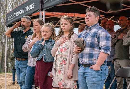 U.S. Army SFC Josh Ferguson, his wife Danny, and their children participate in the national anthem during a groundbreaking ceremony Thursday.