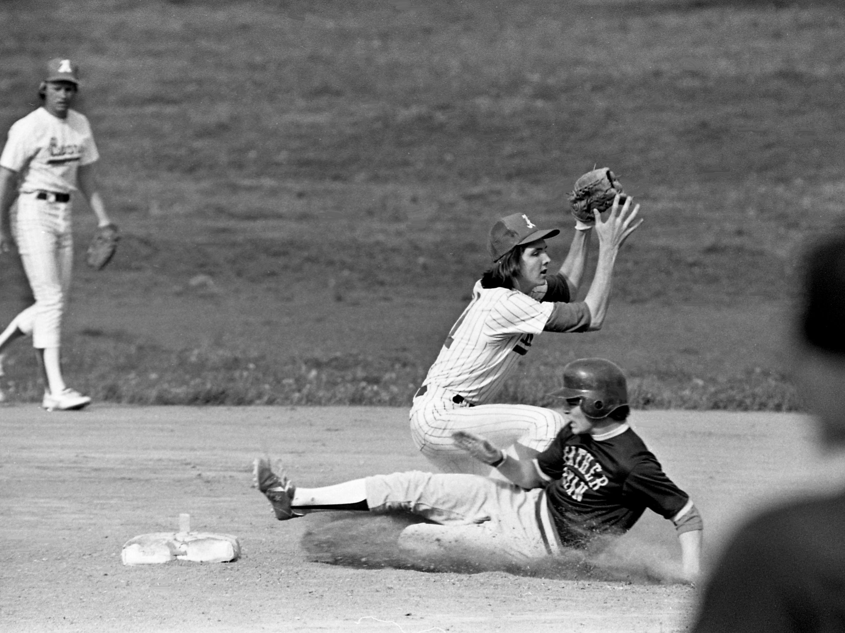 Father Ryan High baserunner Mike McIntyre safely slides into second base despite the effort of Antioch High's Bobby Hudson during Father Ryan 7-2 victory over District 11 rival Antioch on April 18, 1979.
