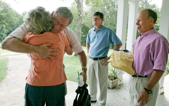 FedEx First Officer Jim Tucker hugs Susan Sanders after greeting Capt. David Sanders (center) and Flight Engineer Andy Peterson (right) on Aug 30, 2007. The three crew members of FedEx flight 705, which underwent an attempted hijacking in 1994, reunited at the Sanders' home.