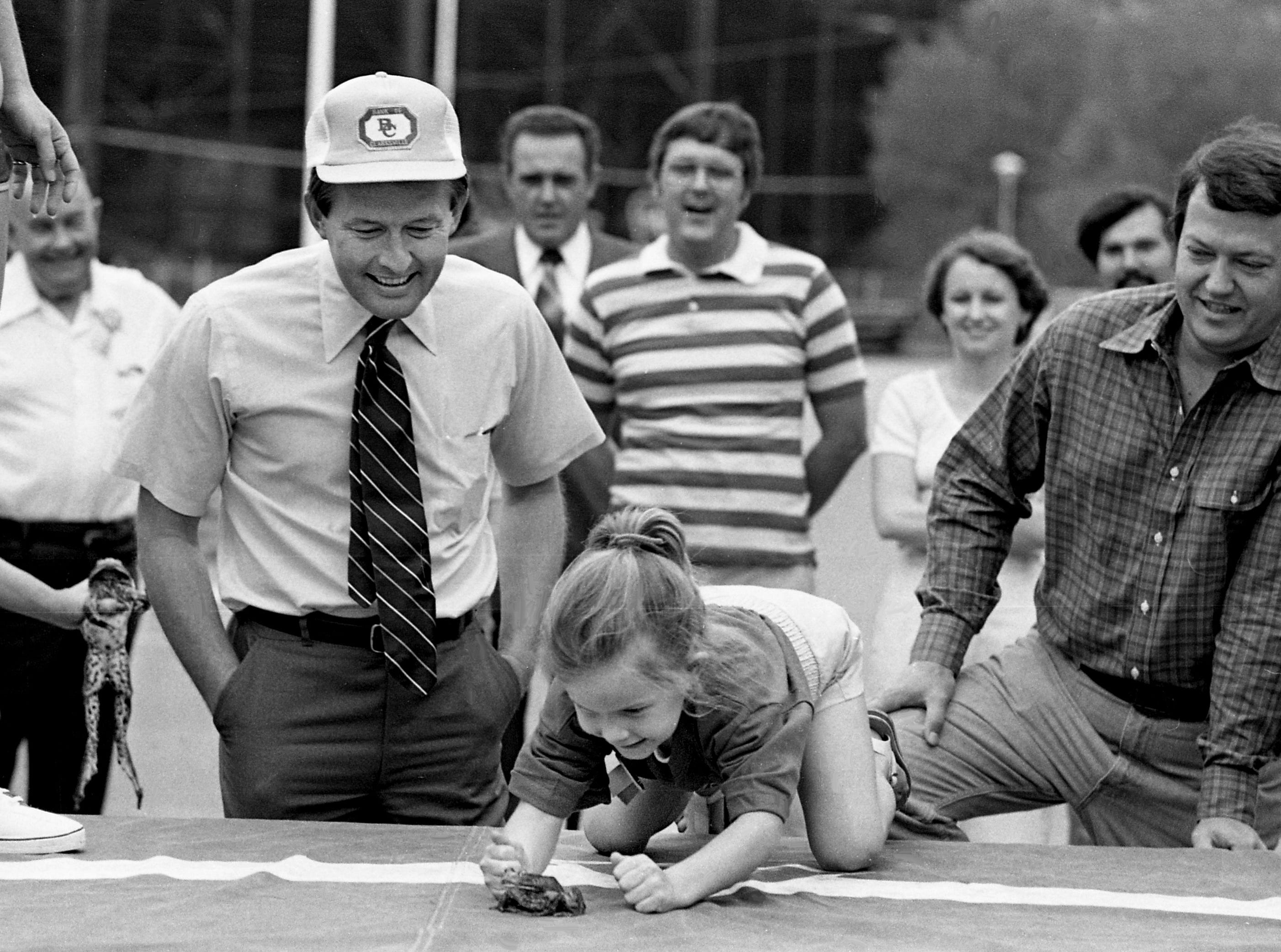 Gov. Lamar Alexander, left, looks on as his daughter Leslie attempts to get her frog to jump during the United American Bank's first annual Frog Jump in the parking lot of the bank's West End branch April 21, 1979.