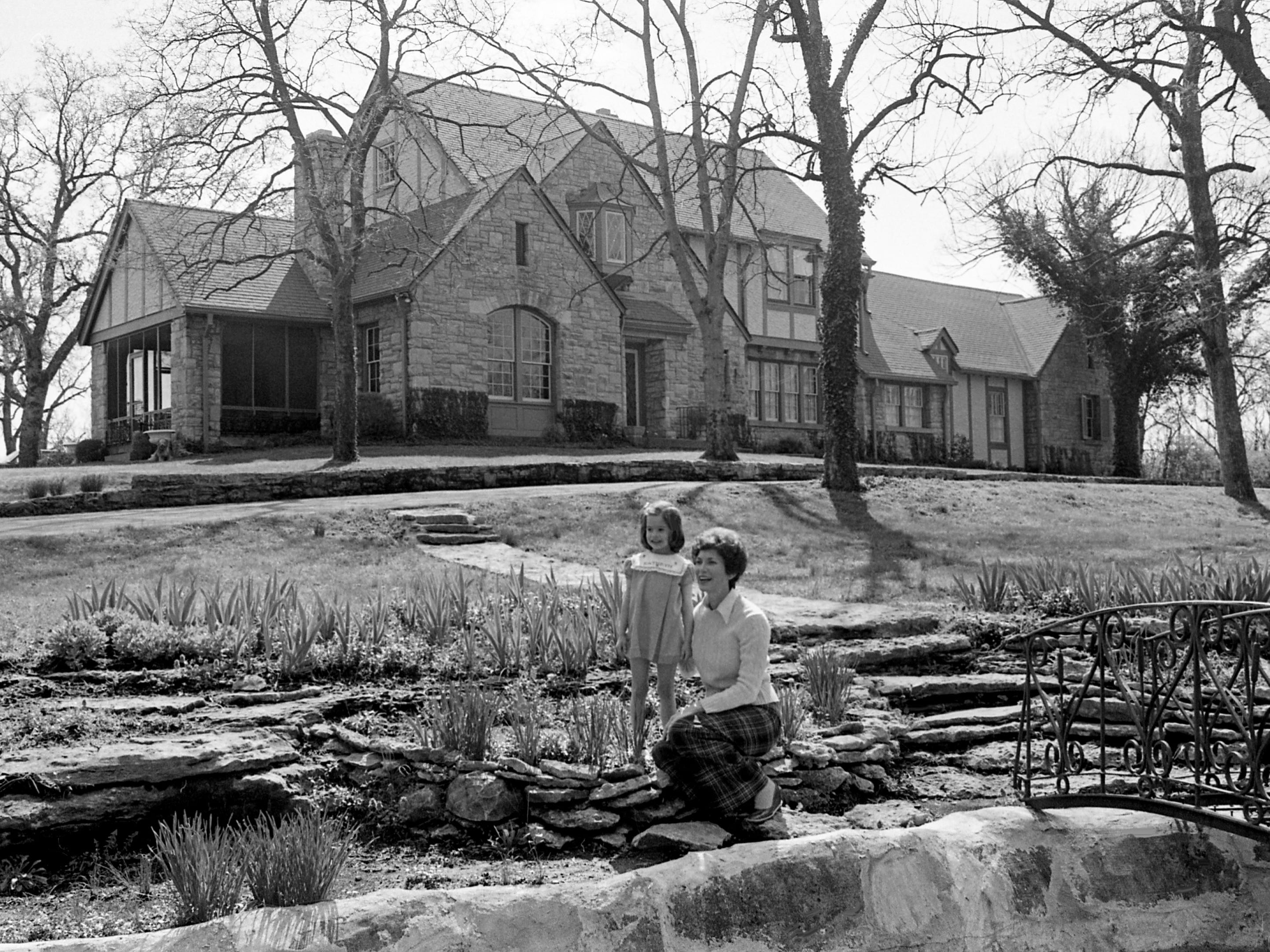 Mrs. Thompson B. Patterson and daughter Kathryn look at the spring plants April 3, 2979, in their English garden built into the original breastworks dug for the Battle of Nashville. The classic stone and timber house, Windycrest, at 1811 Woodmont Blvd., will be open to the public on the Historic Belmont Tour of Homes on April 25.
