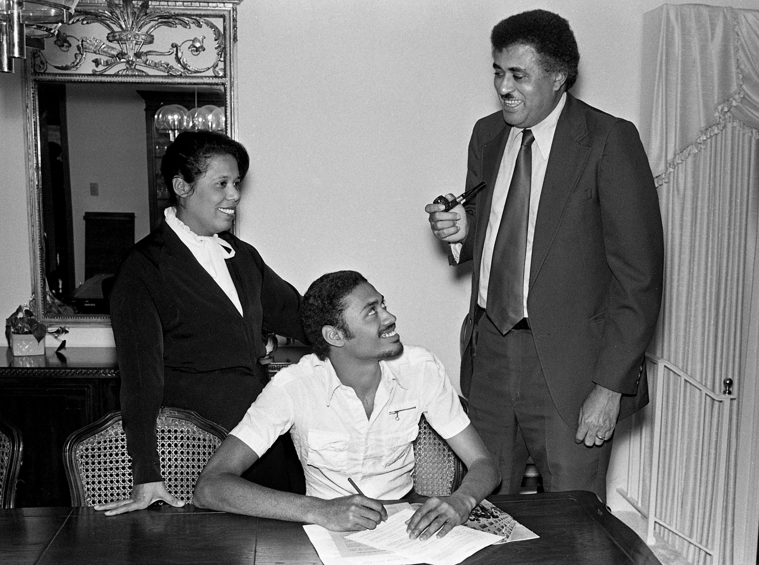 Tennessee State University President Frederick Humphries, right, and his wife, left, look on as their son, Fred Humphries, signs a basketball grand-in-aid with Morehouse College in Atlanta at their home April 24, 1979. The younger Humphries was a star for University School of Nashville.