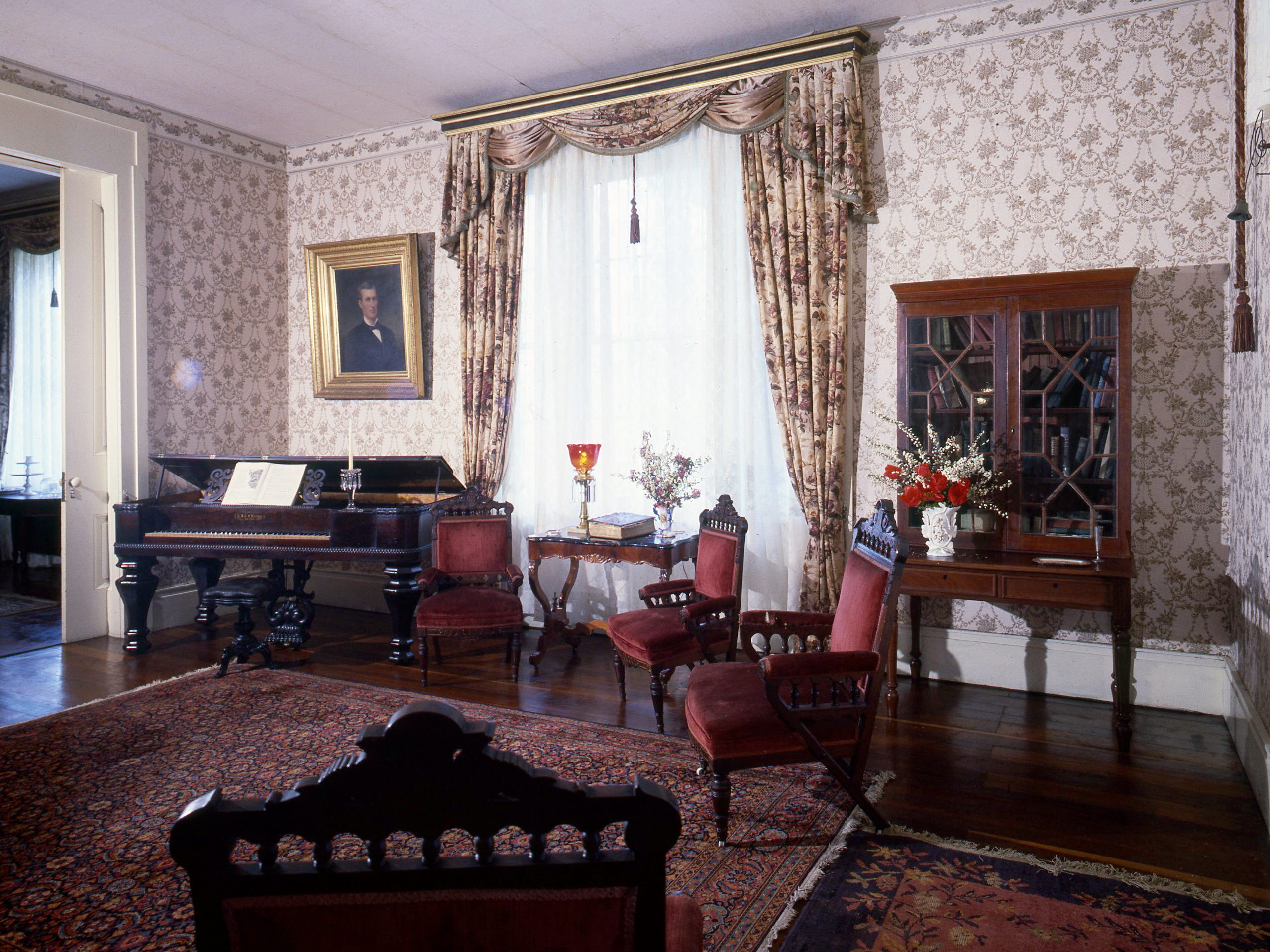 """The living room of the """"Rosemont"""" home, pictured here on April 12, 1979, still has its original furniture and decorative accessories from when it was built and completed in 1842 by Judge Jo Conn Guild. The velvet-upholstered Victorian chairs and square piano hark back to the early days of the house. The portrait on the left is of Walter J. Guild, son of the first owner, who was injured in the Civil War and died young. The portrait was painted by Nicola Marshall in 1880."""