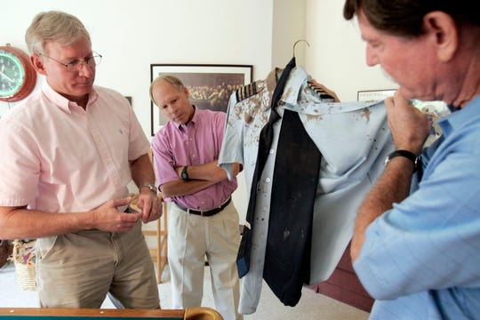 FedEx First Officer Jim Tucker (left) and Flight Engineer Andy Peterson (center) look at the blood-stained uniform that Capt. David Sanders was wearing when the three were part of the attempted hijacking of FedEx Flight 705 in 1994. The three reunited at the Sanders' home on Aug. 30, 2007.