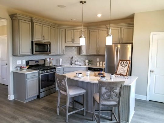 An eat-in kitchen with an island, stainless appliances and decorative cabinets are features in this model home kitchen in Burkitt Commons. Kitchens in Burkitt Ridge will have similar amenities.