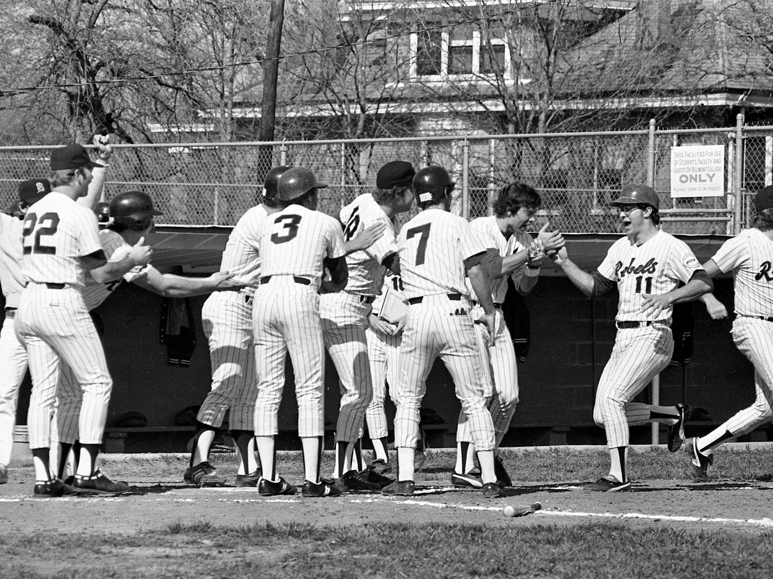 Belmont College catcher Charlie Crain (11) receives congratulations from his teammates after hitting a grand slam home run in the first inning of their 8-0 victory over city rival Trevecca College at Belmont on April 5, 1979.