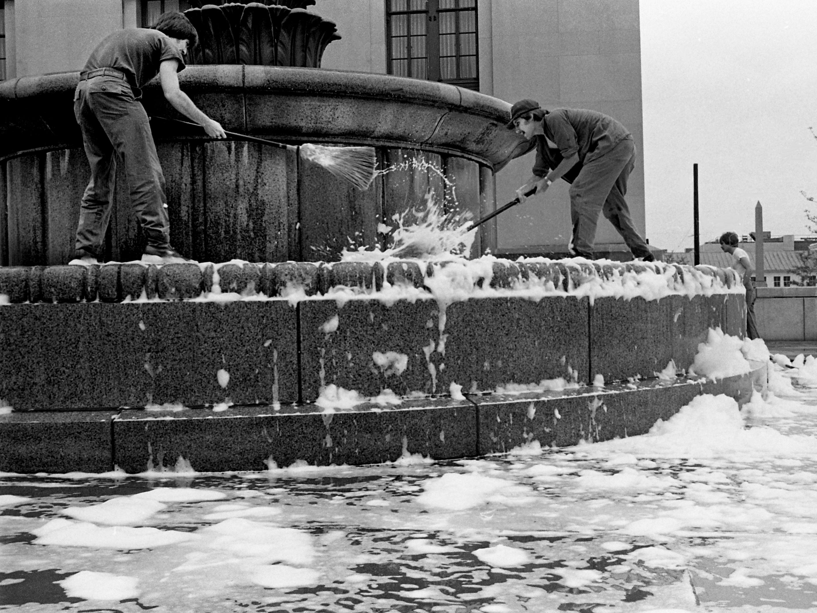 Providing a golden, if somewhat public, opportunity for someone to get a free bath, workers convert a Metro Courthouse fountain into a sudsy tub as they clean its basin April 25, 1979.
