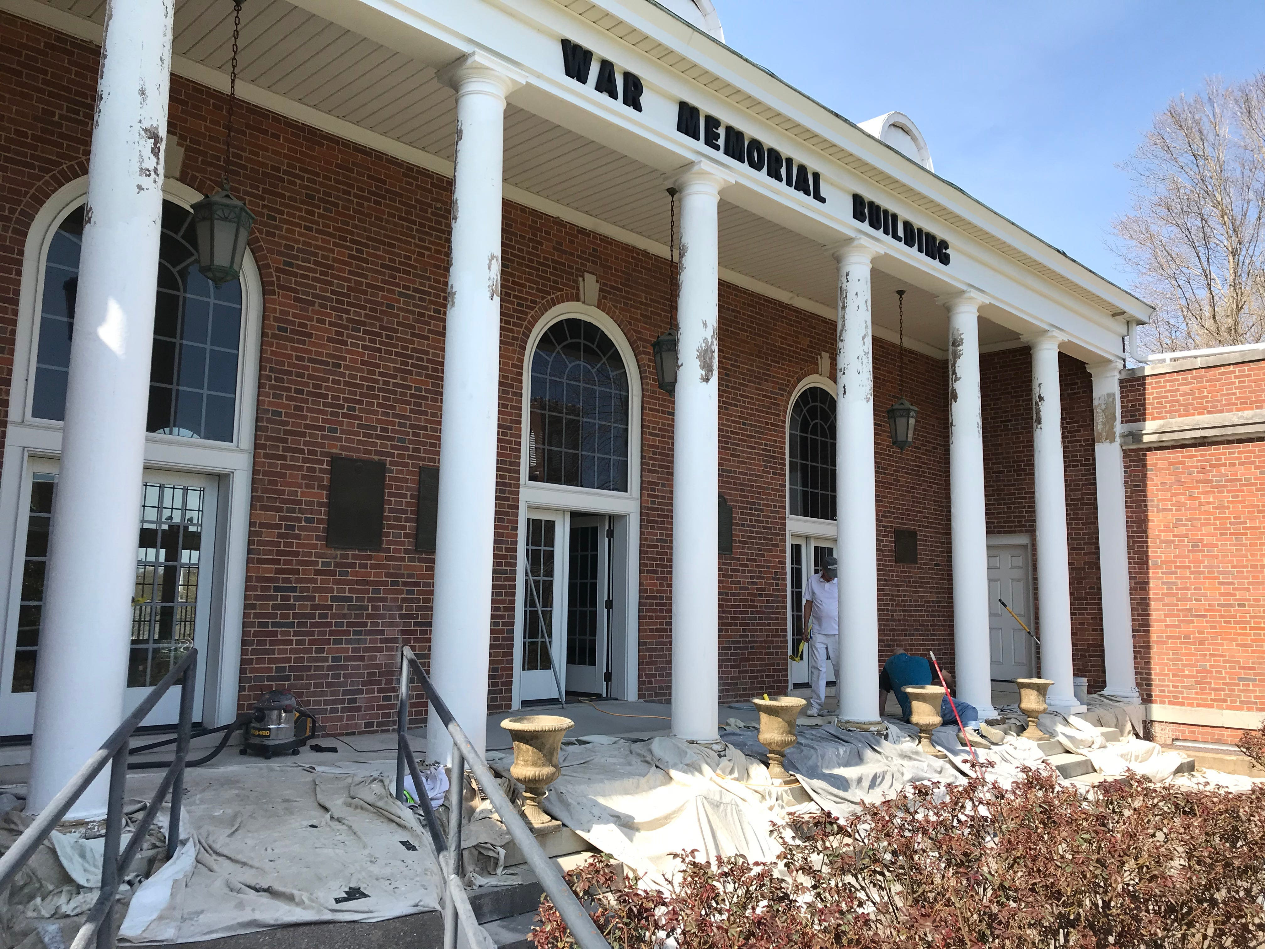 The front of the Dickson War Memorial Building gets a touch up while the back, basement is readied for the Chamber of Commerce's move.