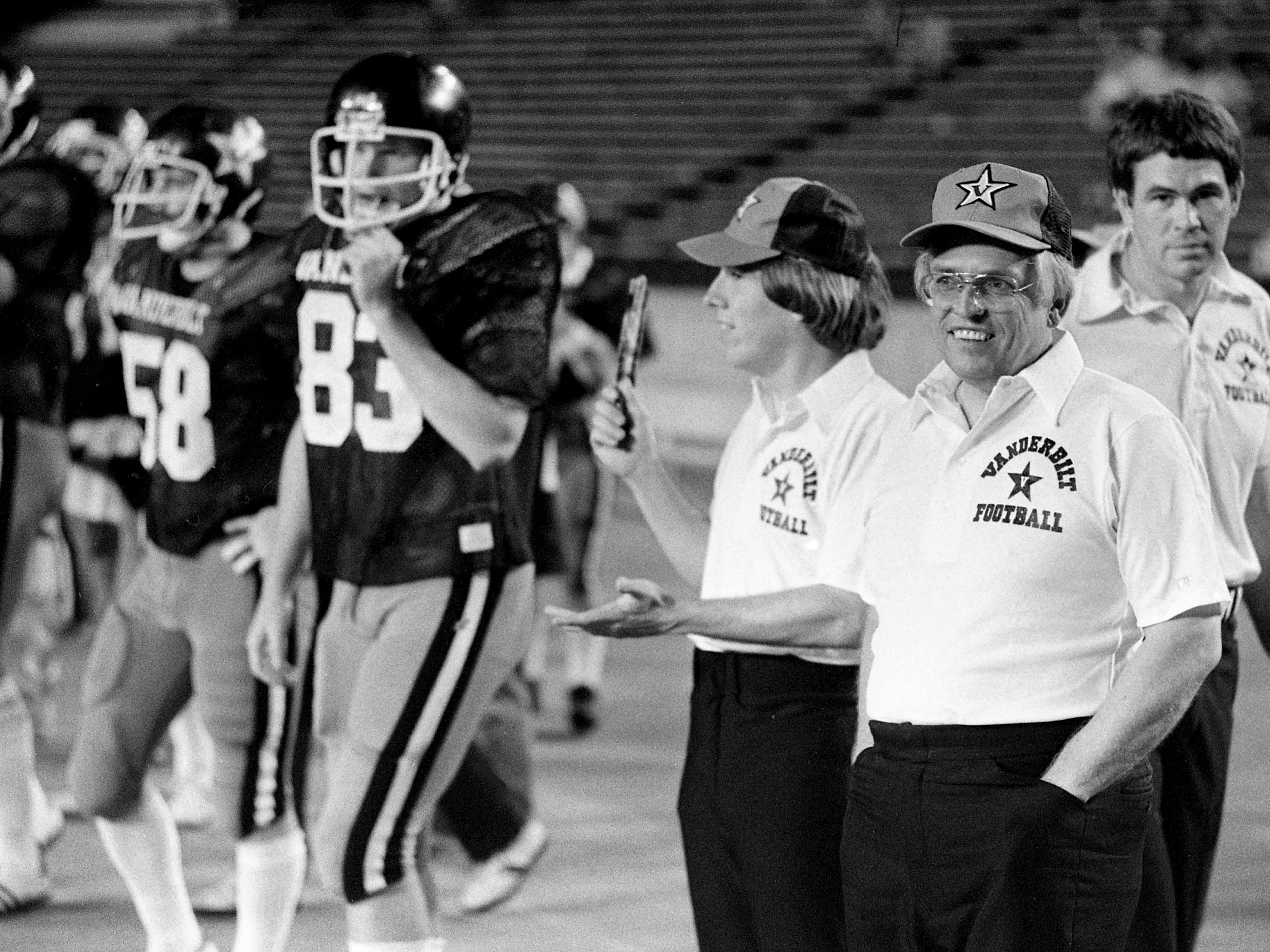 The Tennessean sportswriter Jimmy Davy, front right, and the Nashville Banner sportswriter Tom Robinson, center, both honorary media coaches for the Black Team, look on before the start of the annual Vanderbilt spring football game at Dudley Field on April 21, 1979.