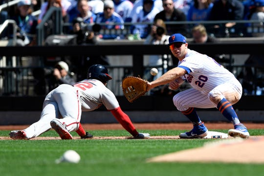 Washington Nationals runner Juan Soto slides back to first before New York Mets first baseman Pete Alonso (20) can place the tag during the Mets home opener against the Washington Nationals on Thursday, April 4, 2019, in Flushing, NY.