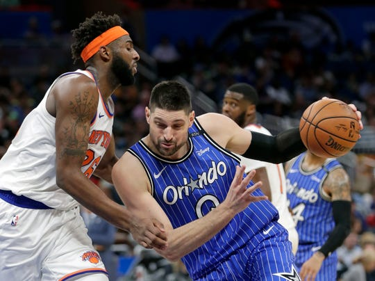 Orlando Magic's Nikola Vucevic, right, drives to the basket against New York Knicks' Mitchell Robinson during the second half of an NBA basketball game Wednesday, April 3, 2019, in Orlando, Fla. (AP Photo/John Raoux)