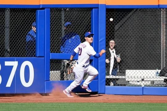 New York Mets' Michael Conforto attempts to run down a ball in the outfield. The New York Mets lose their home opener against the Washington Nationals, 4-0, on Thursday, April 4, 2019, in Flushing, NY.