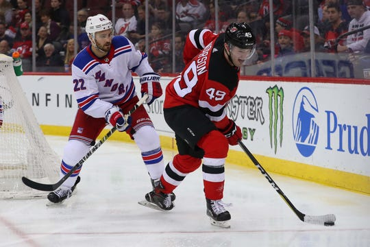 Apr 1, 2019; Newark, NJ, USA; New Jersey Devils right wing Joey Anderson (49) skates with the puck while being defended by New York Rangers defenseman Kevin Shattenkirk (22) during the second period at Prudential Center.