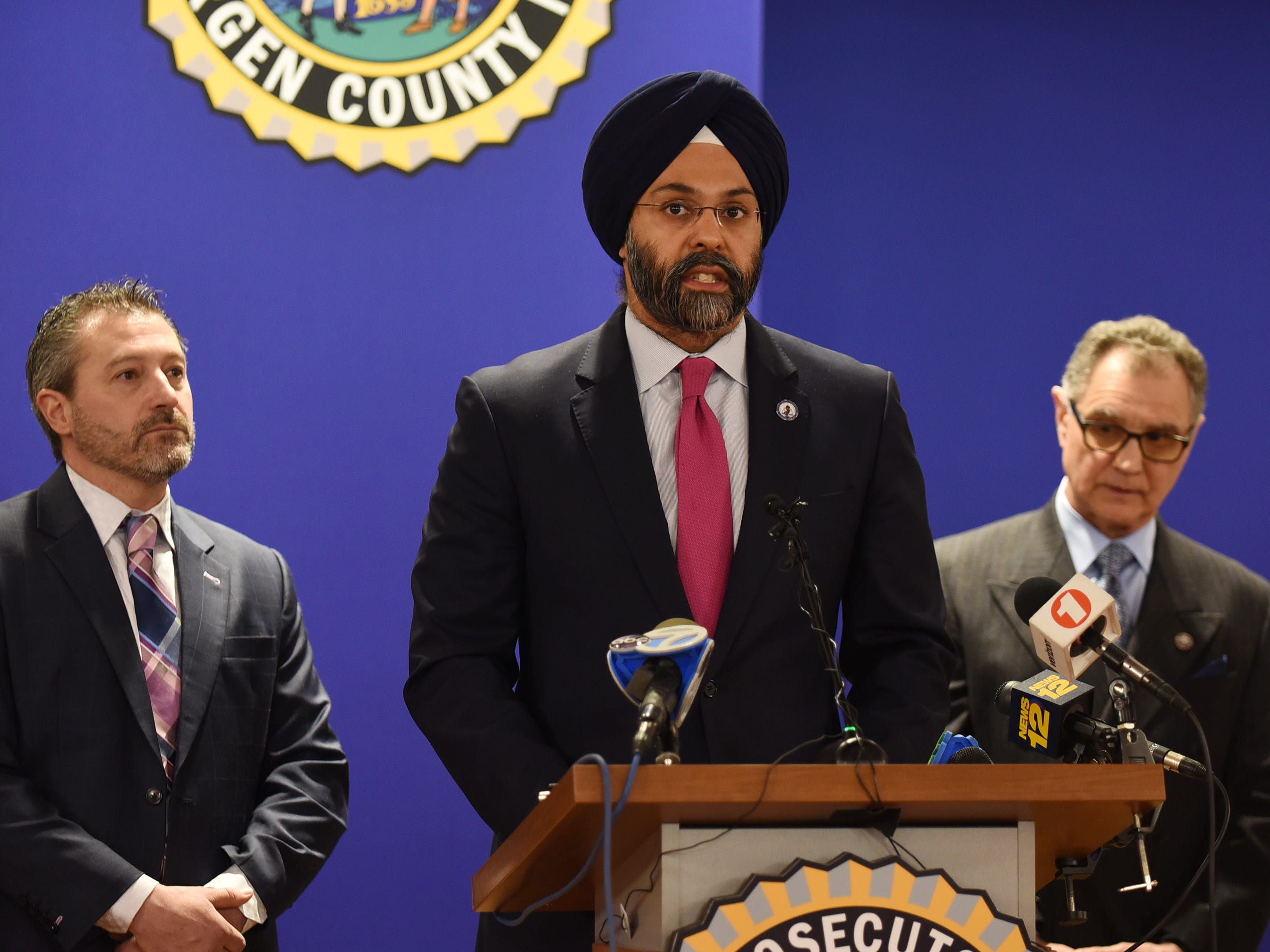 Attorney General Gurbir S. Grewal speaks to the media as Robert Anzilotti (L), Chief of Detectives at Bergen County Prosecutor's Office and Dennis Calo (R), Acting Bergen County Prosecutor, listen during a press conference to announce the expansion of the Bergen County Cold Case Homicide Unit at Bergen County Plaza in Hackensack on 4/4/19.