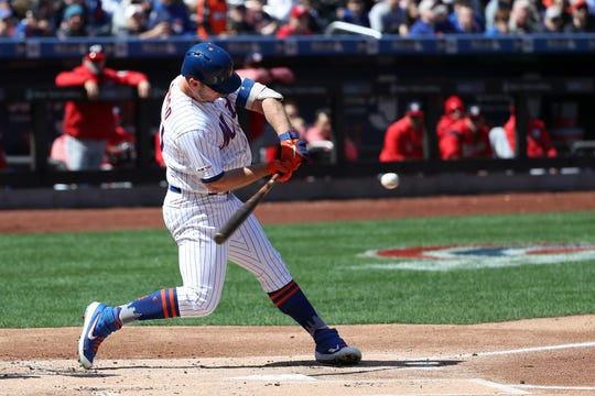 Pete Alonso (20) of the New York Mets reaches first base on an error in the first inning against Washington Nationals fails to make a play at first base on April 04, 2019 during the Mets home opener at Citi Field in the Flushing neighborhood of the Queens borough of New York City.