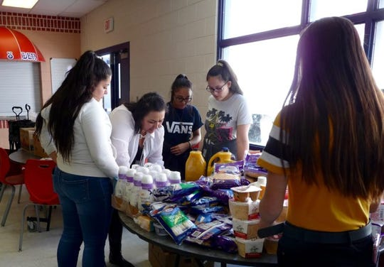 """Lynn Community School Coordinator Sylvia Chavez, second from left, works with students to set up Lynn Middle School's monthly food pantry for neighborhood residents. The students """"shop"""" for community members, pack the food up and carry it to their customers' cars."""