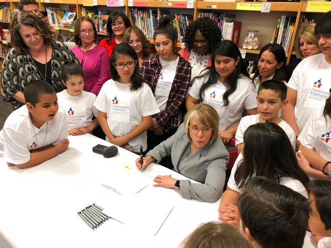 New Mexico Gov. Michelle Lujan Grisham, seated, with pen, signs legislation to raise teacher salaries and increase annual spending on public schools by almost a half-billion dollars on Wednesday, April 3, 2019, at Salazar Elementary School in Santa Fe, N.M. State lawmakers are contending with a court order to increase funding for at-risk students. New Mexico is one of several states where parents have turned to the judiciary to address frustrations over state budget priorities and the quality of education.
